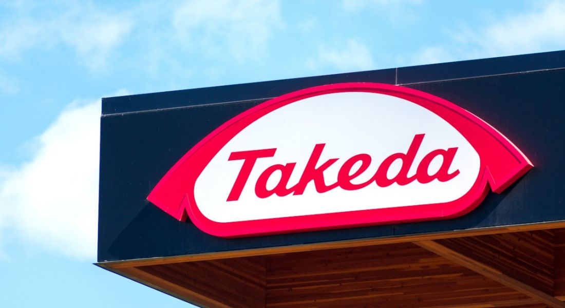 A sign of the Takeda logo on the top of an office building against a blue sky.