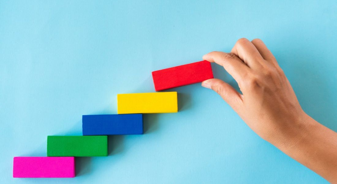 A hand places a red rectangular block on top of a bunch of other colourful blocks in the shape of a staircase against a blue background.