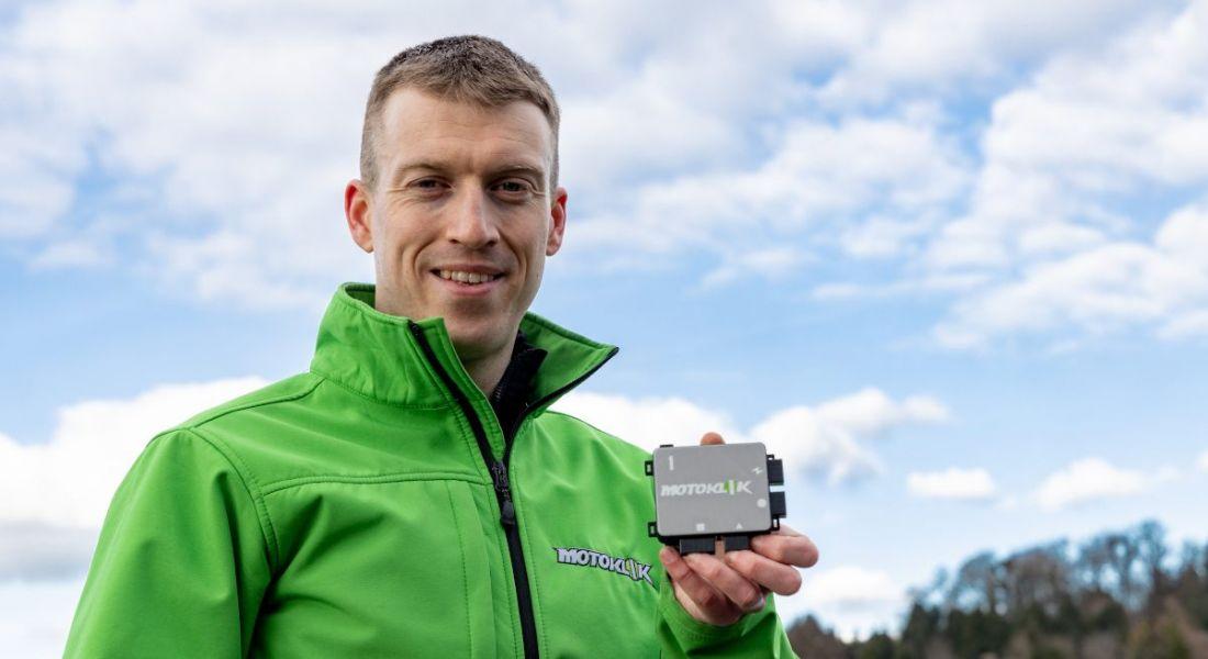Jens Köpke holds up the palm-sized Motoklik device. He is wearing a high-vis green jacket.