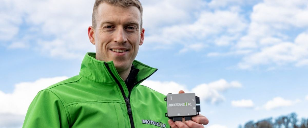 Jens Köpke holds up the palm-sized Motoklik device. He is wearing a high-vis green jacket.