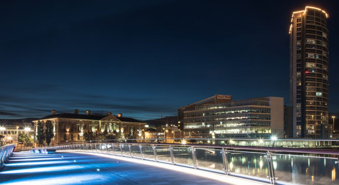 The Belfast cityscape seen from a bridge at night.