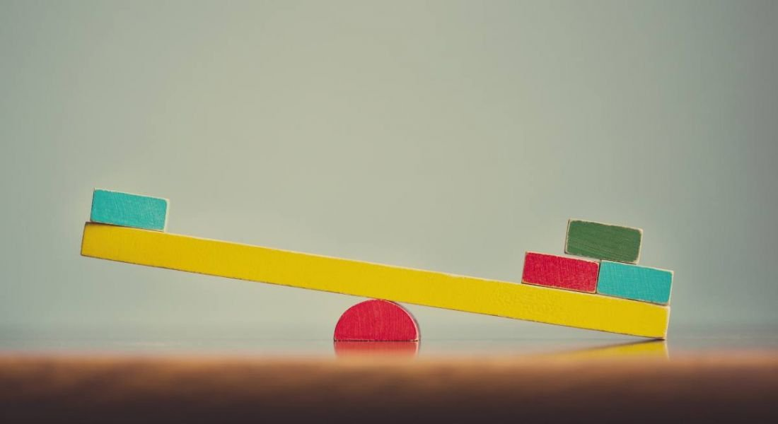 A colourful wooden seesaw is unbalanced.
