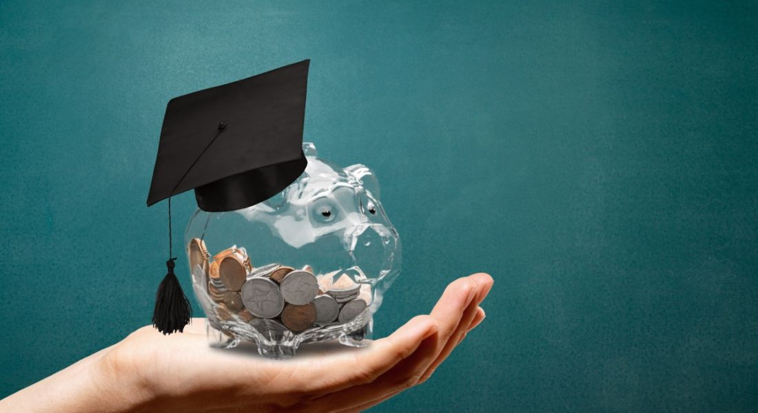 A hand is holding up a clear piggy bank with a graduation hat on it against a green background.