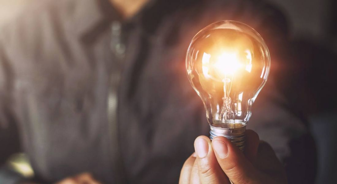 A person is holding a light bulb up to the camera, symbolising using energy while working from home.