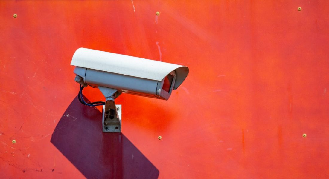 A security CCT camera mounted on a red-painted wall, symbolising workplace surveillance.