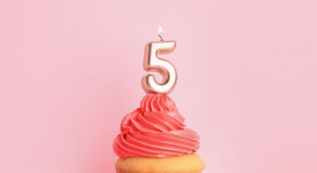 Birthday cupcake with number five candle on pink frosting against a pink background.