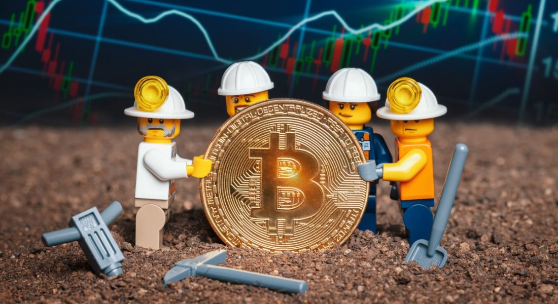 Group of Lego mini miner figurines holding shiny bitcoin together and posing, symbolising the role of a bitcoin programmer or bitcoin engineer.