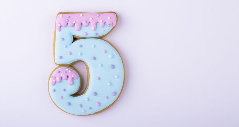 An iced biscuit in the shape of the number five against a lilac background.