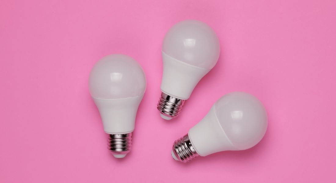 Three LED light bulbs on a bright pink background.