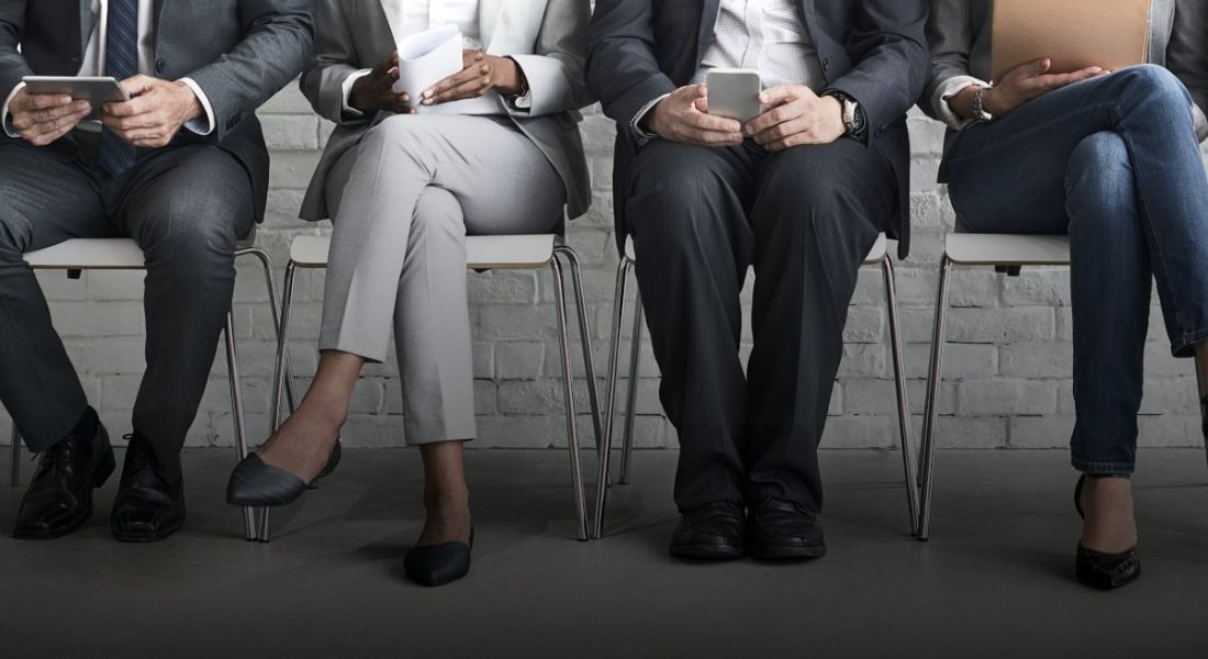 A group of job candidates are sitting side by side in a row, with just their legs and feet in frame.