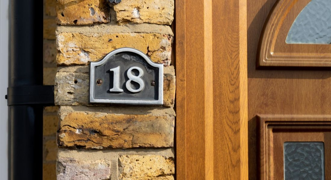 A sign with the number 18 on a brown brick wall next to the front door of a house.