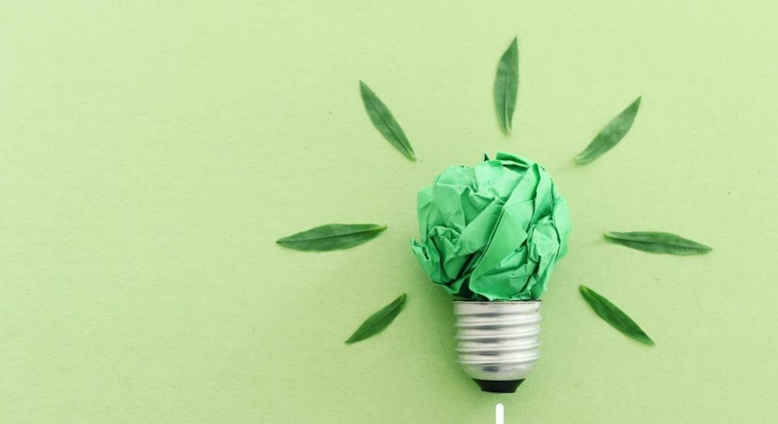 A light bulb made from green paper against a green background.