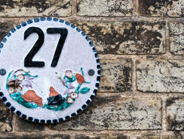 Decorative number 27 plate on a brick wall.