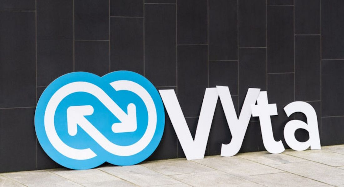 A large cut-out of the new Vyta logo propped up against a grey stone wall.