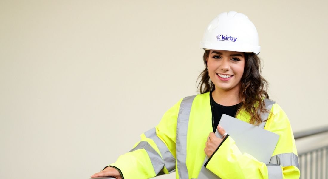 A woman in a high-vis jacket and a hard hat holds a clipboard and smiles at the camera.