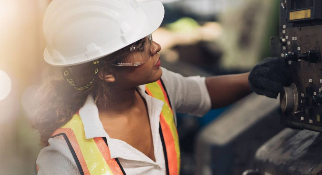 A woman in a hard hat, safety goggles and a high-vis jacket examining a piece of machinery.