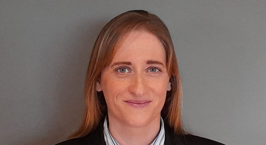 Georgina Molloy, chair of the Women in Engineers Group, is smiling into the camera against a grey background.