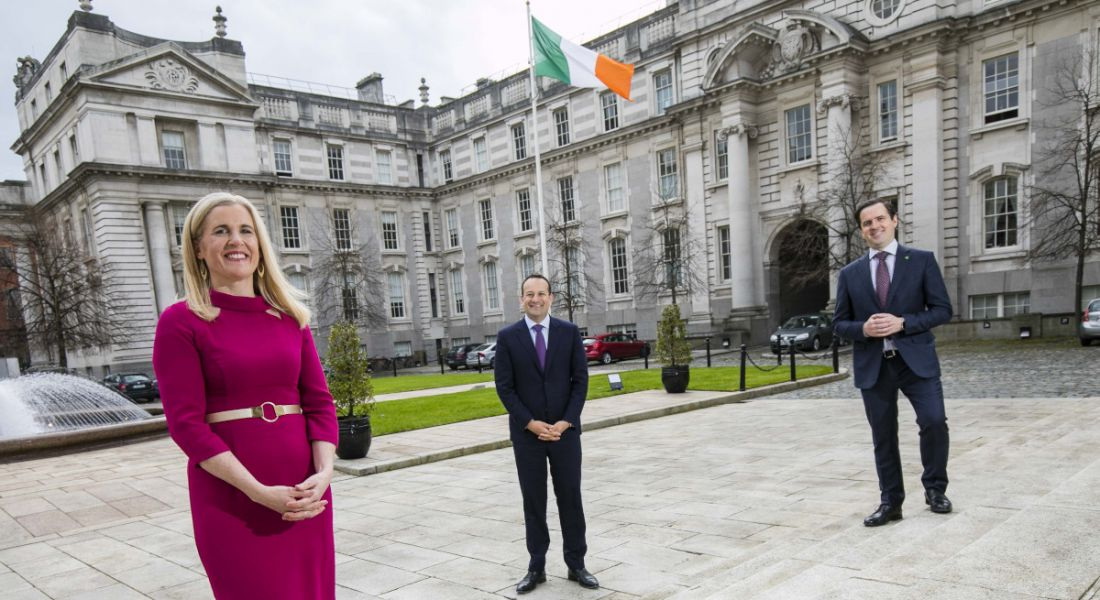 A woman and two men stand two metres apart in front of Government buildings bearing an Irish flag.