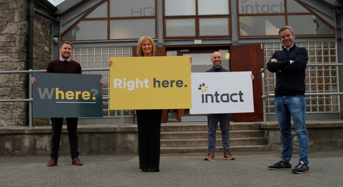 Four team members are standing outside the Intact office in Dundalk, Co Louth, with company signs.