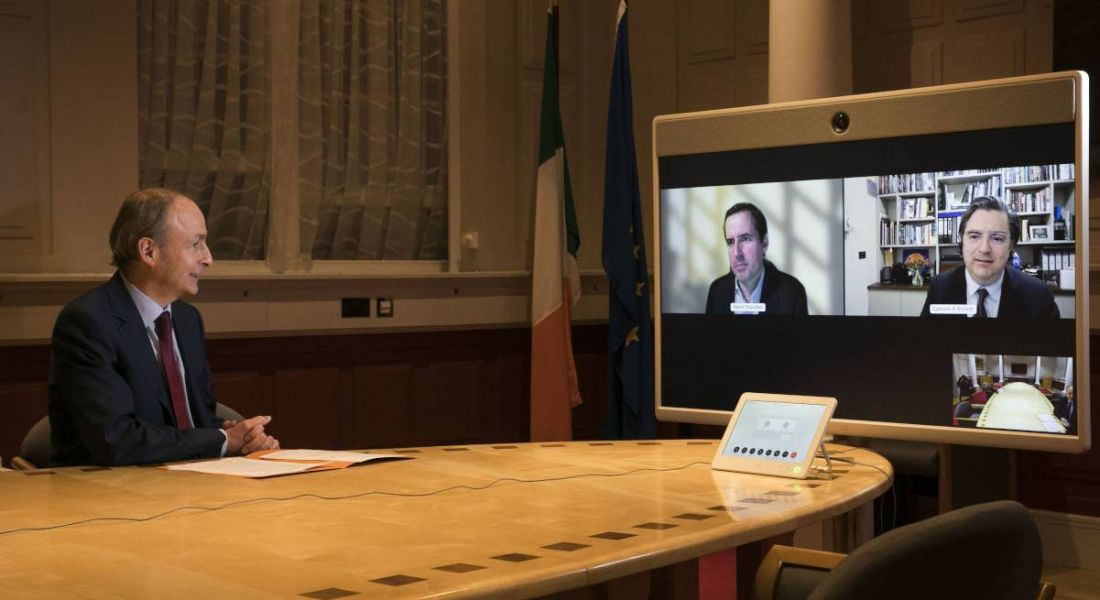 Micheál Martin sits at a conference room table in Government buildings, looking at a large screen for a video call with Martin Shanahan and Eamonn Sinnott.