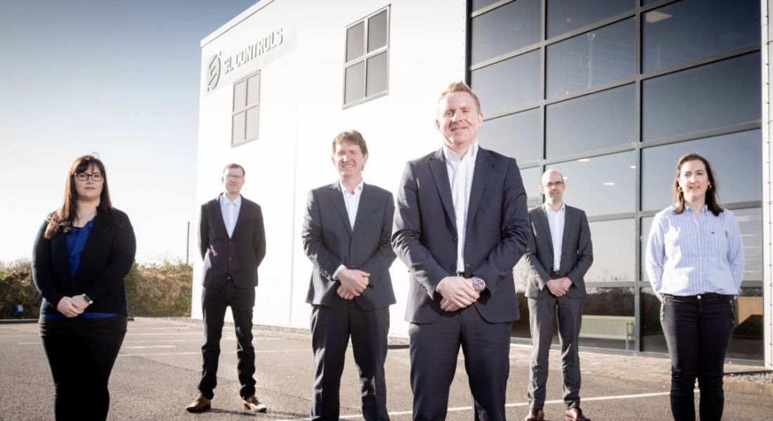 Six people in business attire stand outside in front of a large office building with the SL Controls logo on the side.