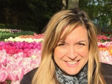 Stacey Wasserman is outdoors in front of colourful flowers in a park.