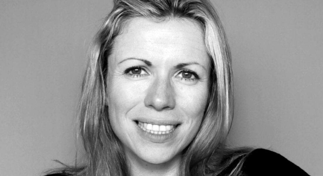 Black and white photograph of Mastercard's vice-president of CX and design, Tansy Murray, smiling into the camera.