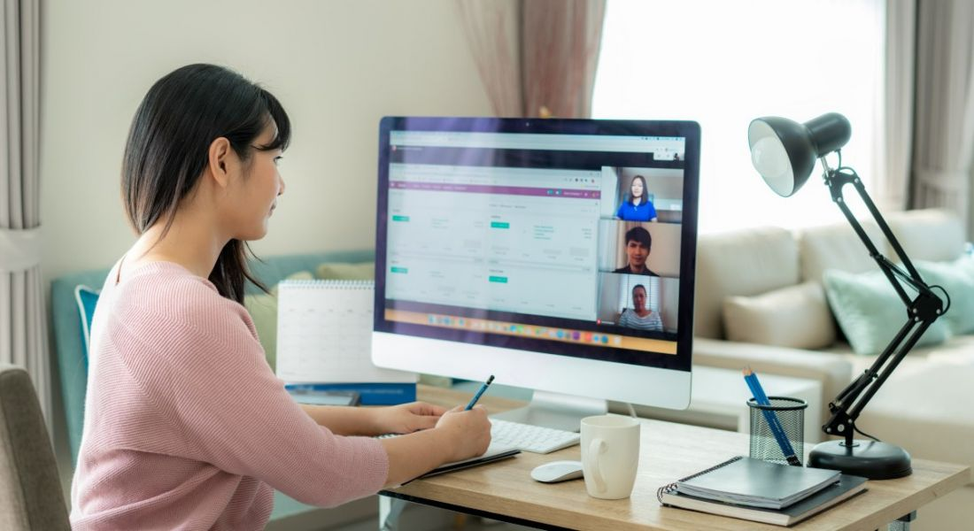A woman remote working at home at a desk with a large computer monitor. She's taking notes while attending a virtual meeting.