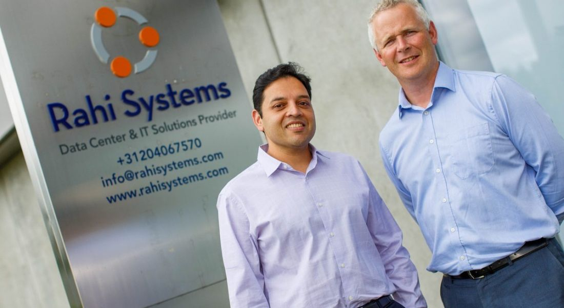 Two men standing in front of a sign with the Rahi Systems logo.