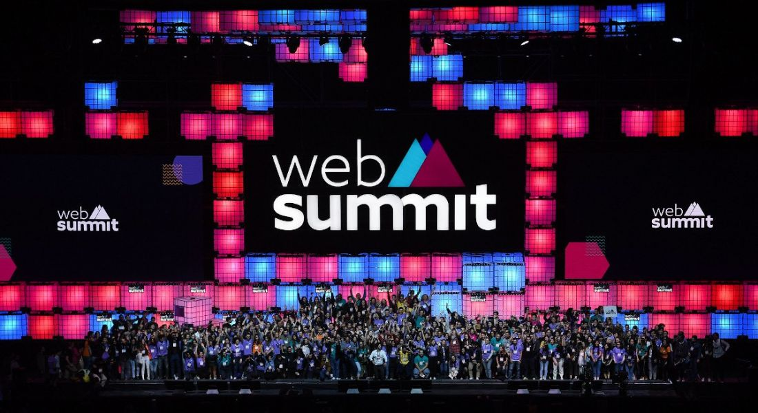 A large crowd of people photographed on a stage decorated with the Web Summit logo and branding.