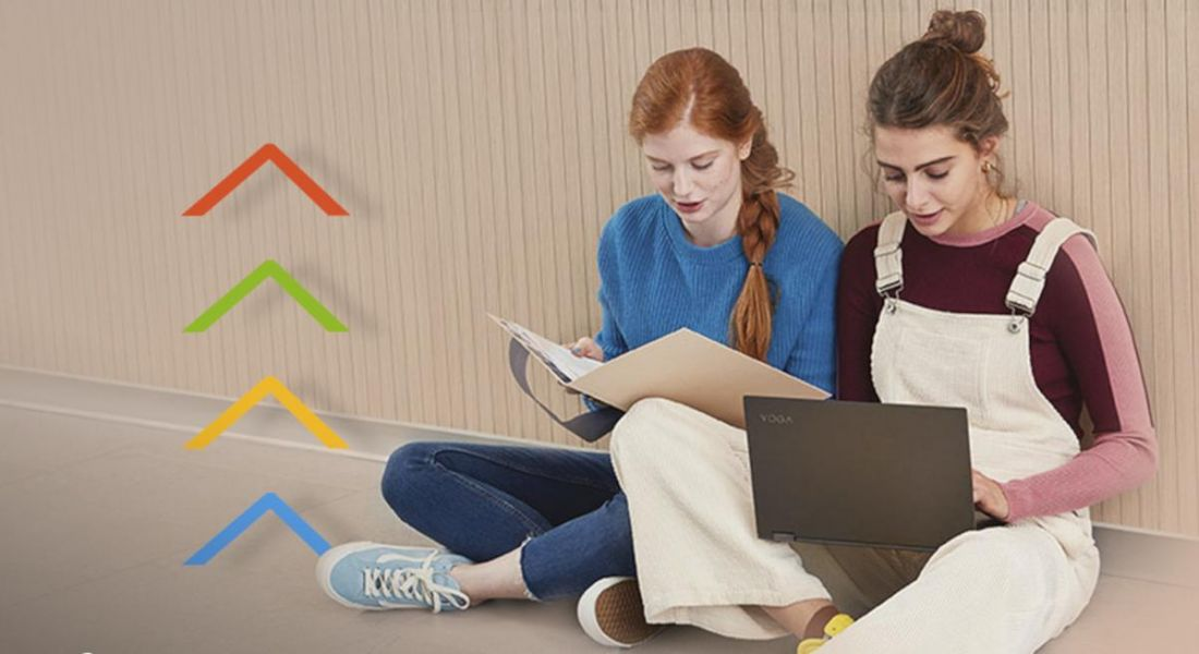 Two teenage girls sitting cross-legged on a floor with laptops as if they are students.