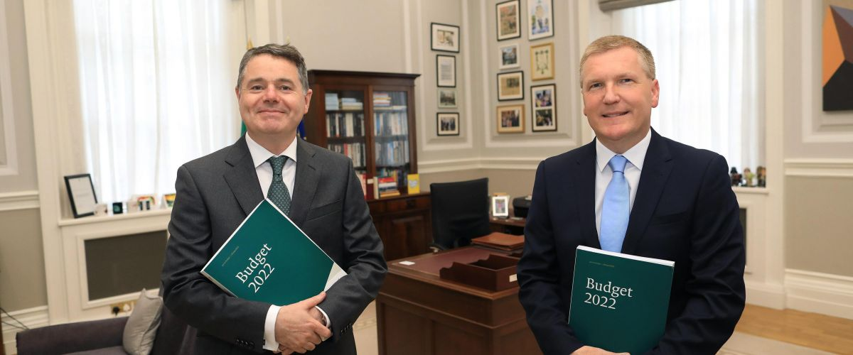 Two men in suits stand in a Government office smiling at the camera. Both are holding green folders that say Budget 2022 on the front.