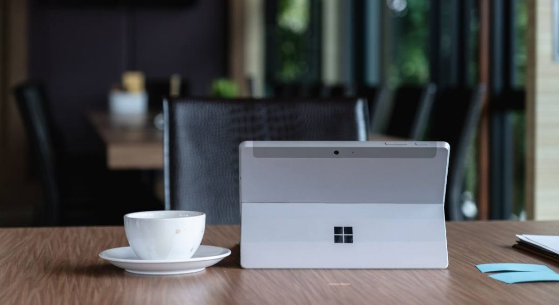 Microsoft logo on a silver tablet sitting on a desk with a coffee cup and paper notes.
