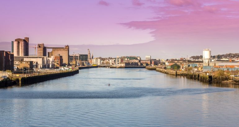 A panoramic view of the harbour in Cork city centre in the morning, with buildings either side.