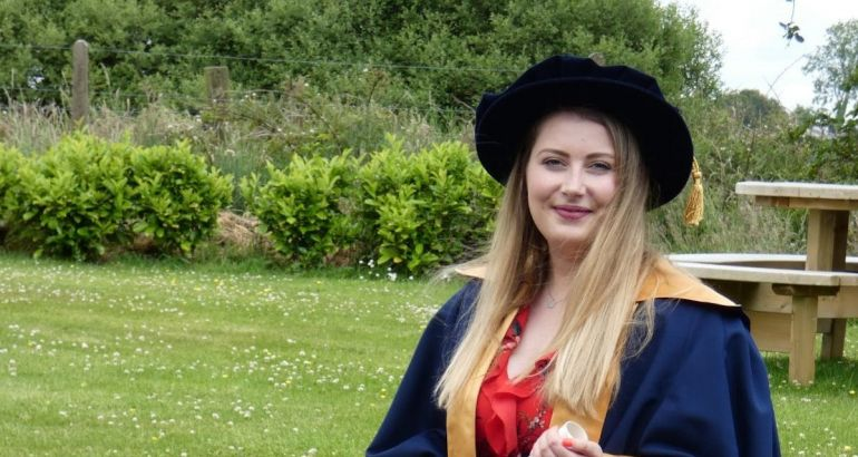 A woman in a doctoral graduation cap and gown standing outside with grass behind her. She is Fiona Hennessy from MSD.