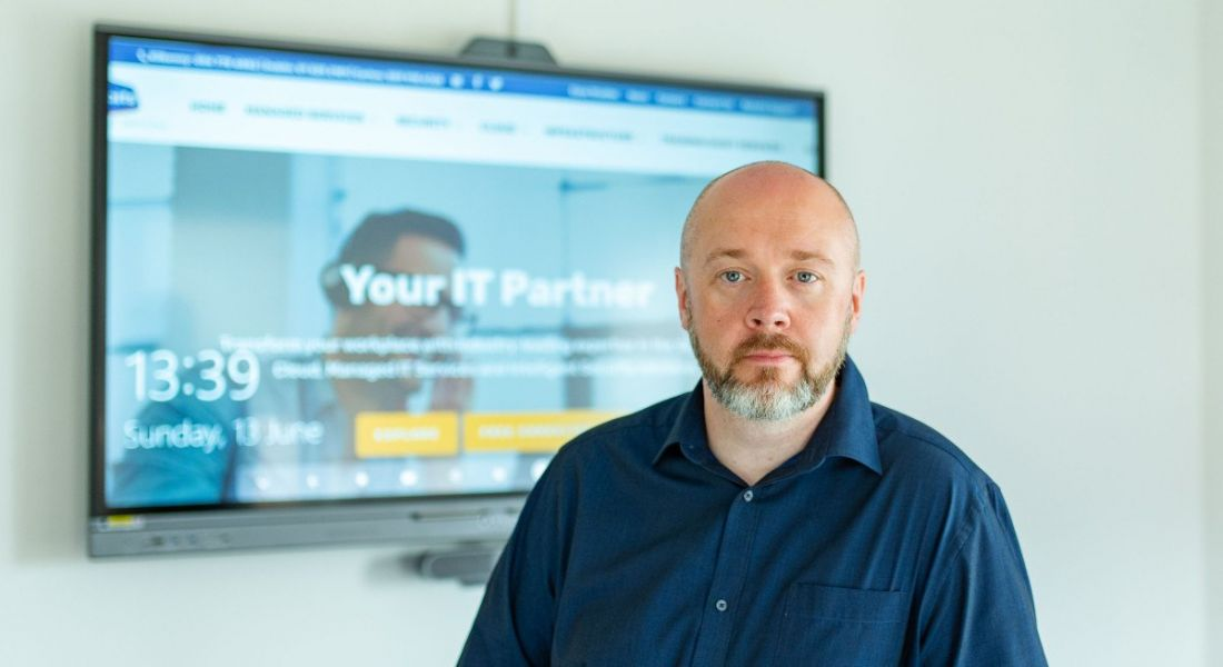 Gavin Dixon, CEO of BITS, standing in a room with a TV monitor behind him with BITS' website displayed on it.