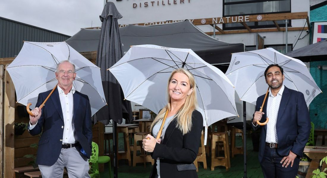 Two men and a woman in business attire stand outside a small distillery, each carrying large white umbrellas to take shelter from the rain.