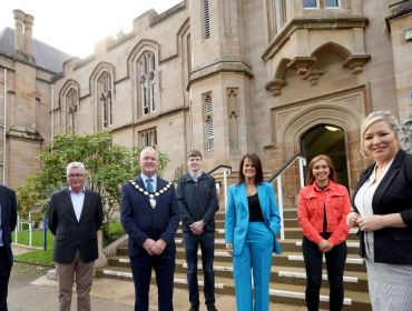 Northern Ireland Deputy First Minister Michelle O'Neill with students and industry stakeholders standing outside a stone building at Ulster University's Magee campus.