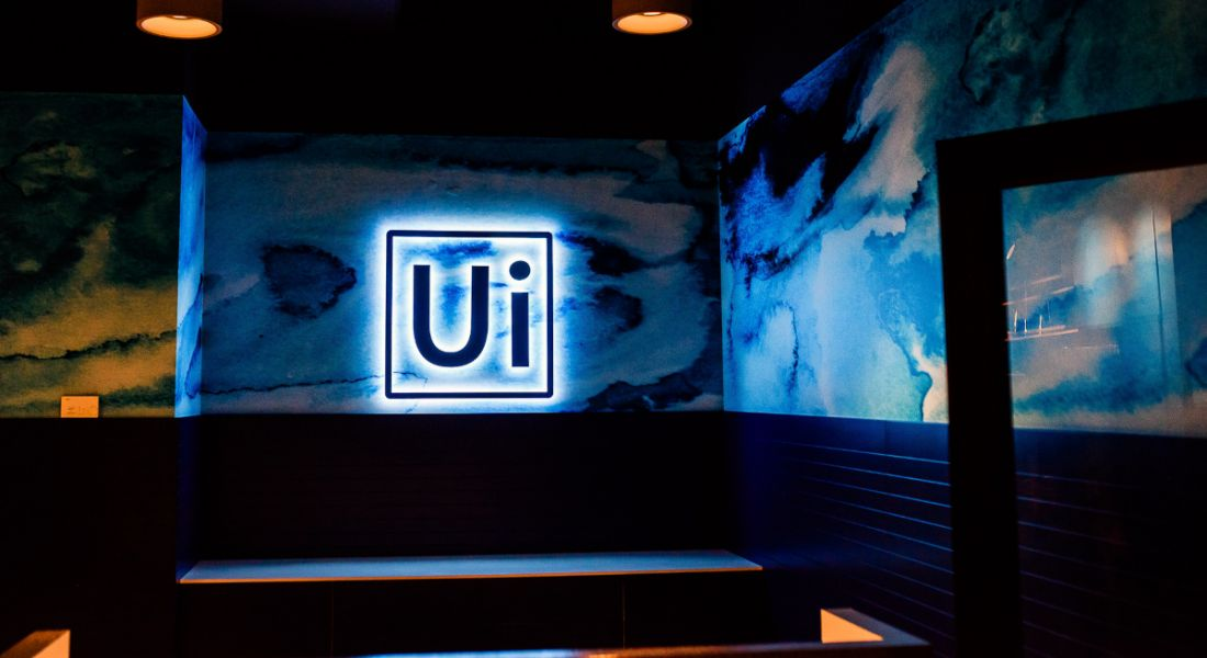 UiPath logo lit up by blue lights on a blue wall.