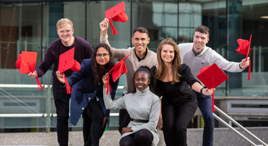 Vodafone Ireland graduate programme participants standing and kneeling in a group outside a glass building waving red graduate caps in the air.