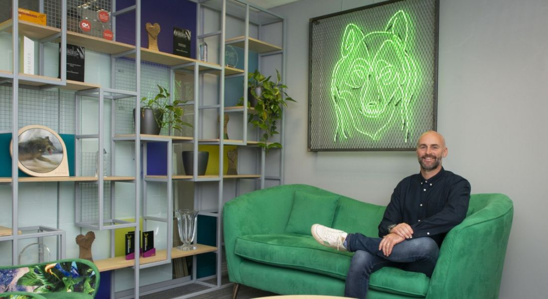 Alan Coleman of Wolfgang Digital sitting in an office reception area on a green couch under a neon green wolf sign.