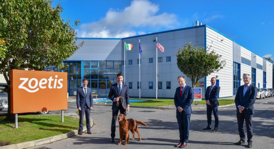 Five men in suits stand outside a large manufacturing facility along with an Irish red setter, held on a leash by one of the men.
