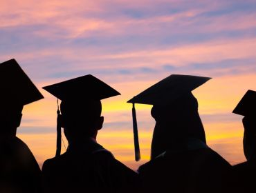 A silhouette of several graduates staring at a colourful sky at sunset.