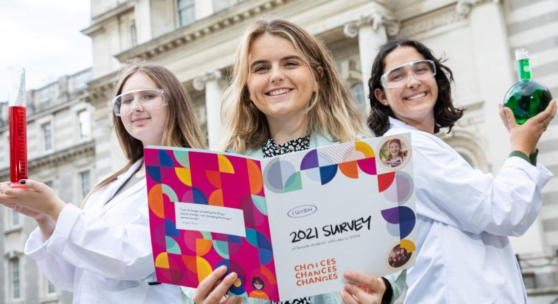 Three young women standing in a row dressed in lab gear and smiling and holding lab equipment outside at the launch of I Wish's report.