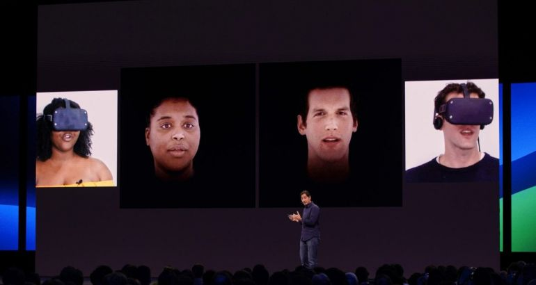 A man stands on stage in front of a large conference audience, with a supersize screen behind him demonstrating Oculus VR technology and headsets.