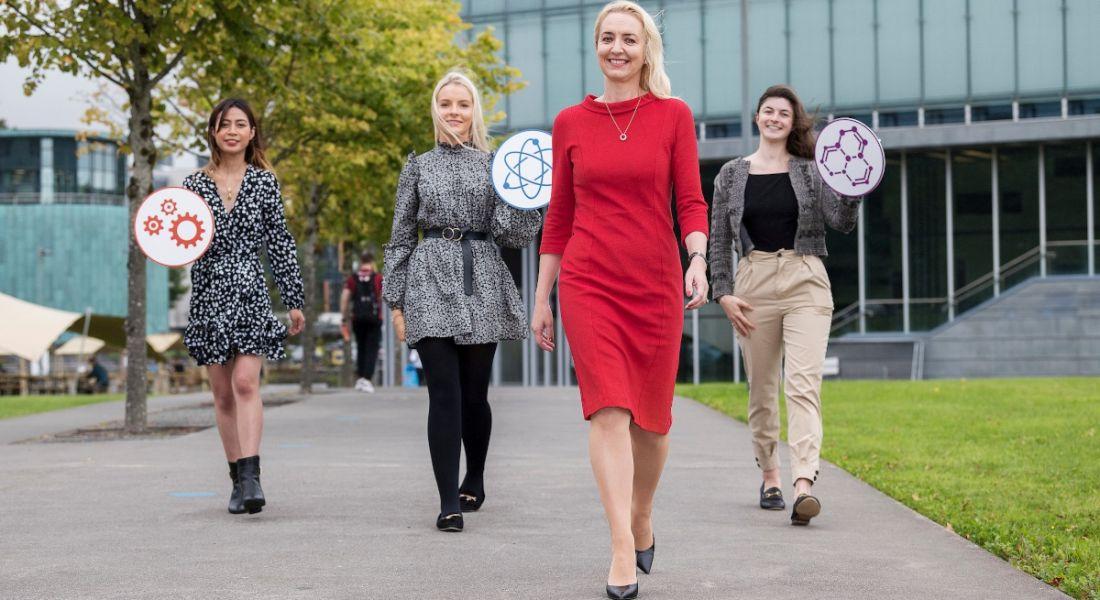Four women walk through a university campus.