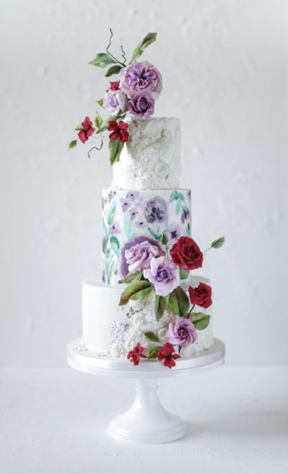 Three tier wedding cake with white icing and floral embellishments