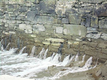 A river runs through the gaps in the pier wall on Cape Clear