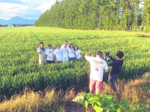 Nuffield scholars having their picture taken with their hosts in a wheat field in Hikkiado, Japan. They were entertained by a young farmers discussion group, taken on tour of the farm and given a beautiful barbecue, which wives and families attended too.
