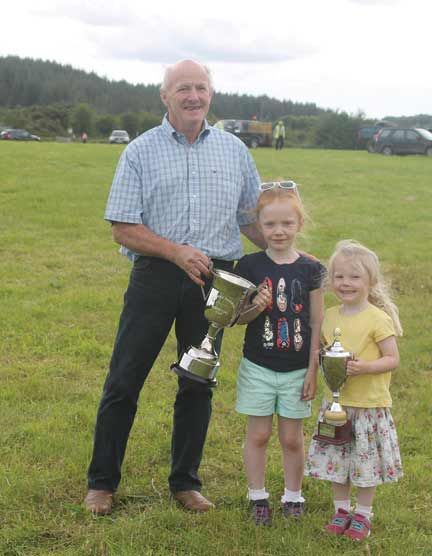 A family affair: Pete Hill, owner of Hail Spartacus, winner of the Thomas Harrington Cup, is pictured with his granddaughters Aoibhe and Sarah Kate Cremin, with the Driver of the Day Cup won by their uncle, Patrick Hill, at Gloun.